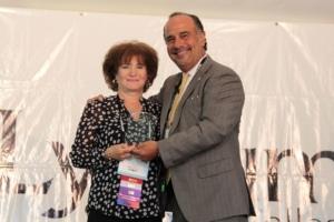 Barbara Dubel receiving an award from Dr. Cordero