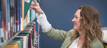 Student grabbing a book